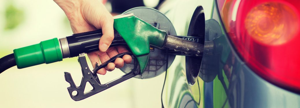 person filling up gas tank in car with green gas station nozzle