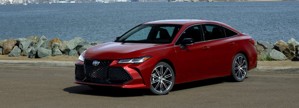 red 2019 toyota avalon parked in front of rocky beach and ocean
