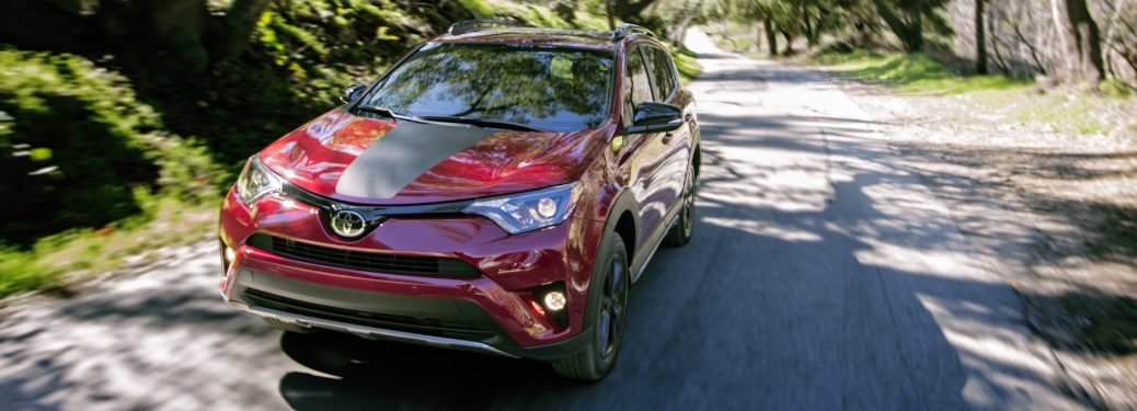 front view of red and black 2018 toyota rav4 driving on forest road