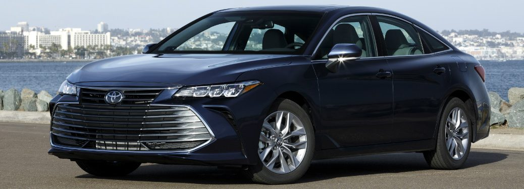front and side view of blue 109 toyota avalon in front of water