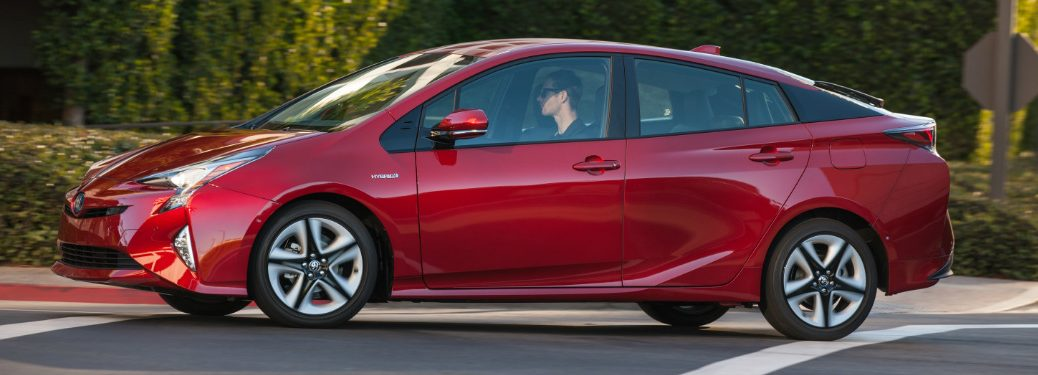 side view of red 2018 toyota prius in front of bushes