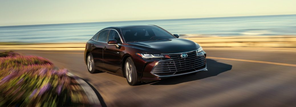 amber 2019 toyota avalon hybrid driving on road next to beach