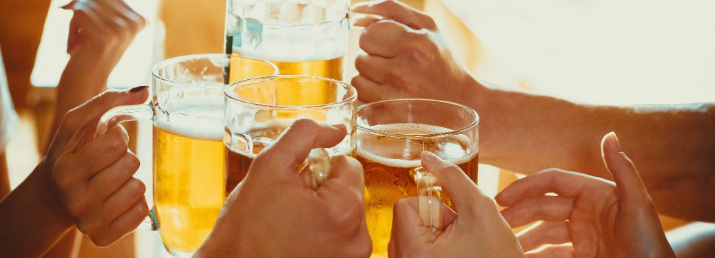 group of hands holding stein mugs with beer cheersing