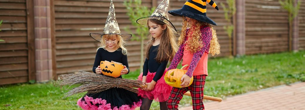 group of young girls in costume trick-or-treating