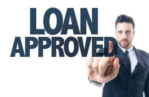 Man standing behind loan approved text