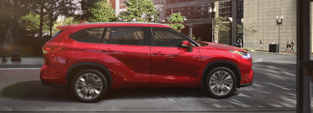 2020 Toyota Highlander red exterior passenger side driving in city streets