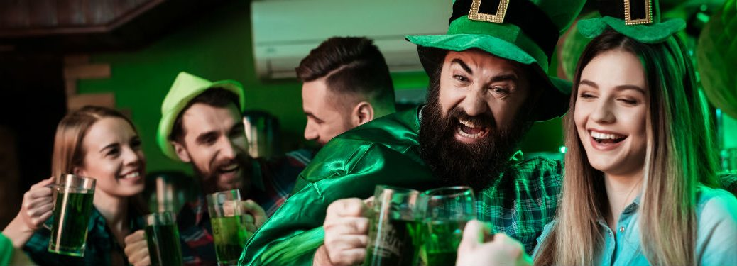 group of friends wearing green and drinking beer