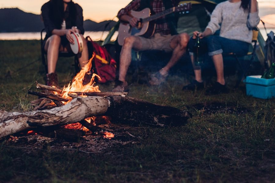Crew sitting by fire camping