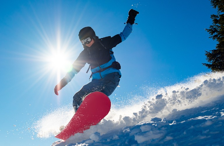 Person snowboarding with sun in background
