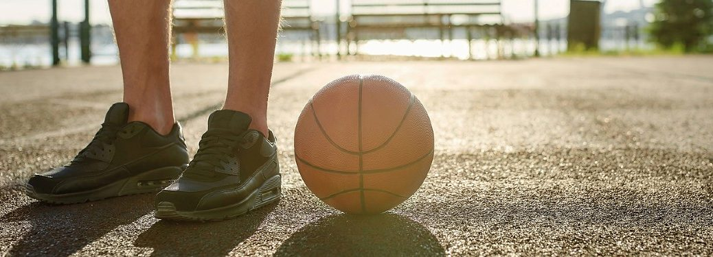 Basketball on ground with person standing next to it