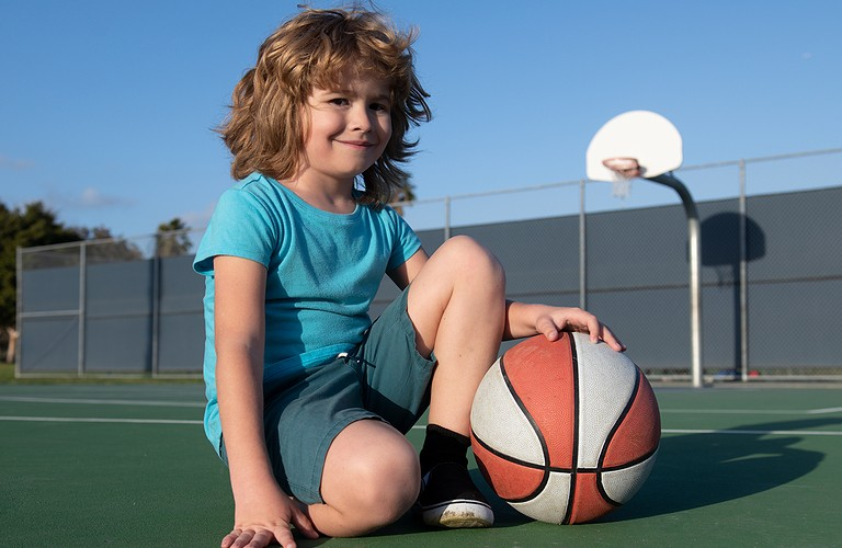 Kid holding basketball at court