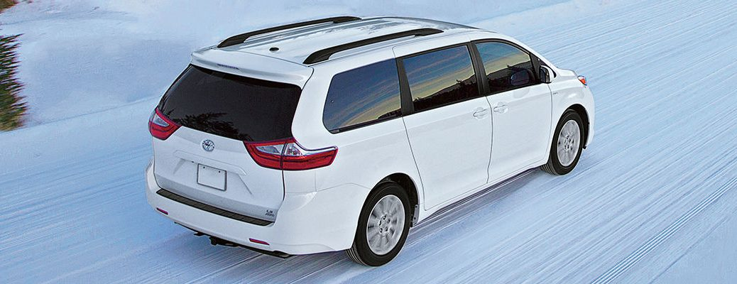Super White 2016 Toyota Sienna LE with All-Wheel Drive on Snow-Covered Road
