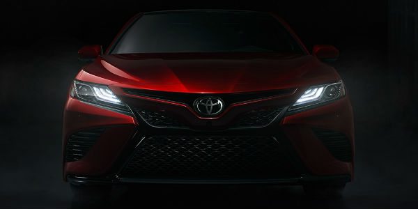 Red 2018 Toyota Camry Grille with headlights on in the dark