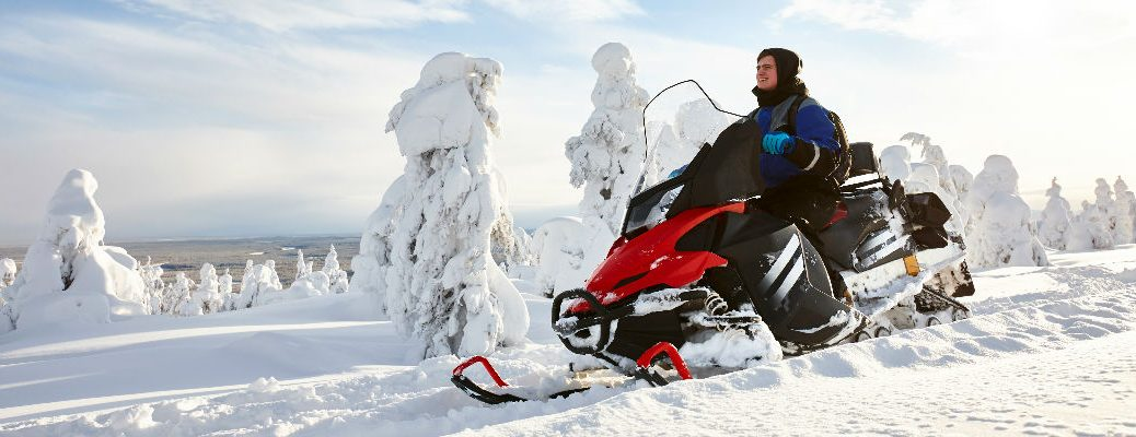 Man on red snowmobile in snow