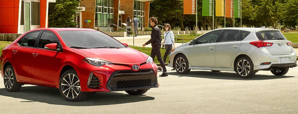 Red 2017 Toyota Corolla in front of building with White 2017 toyota Corolla iM in background
