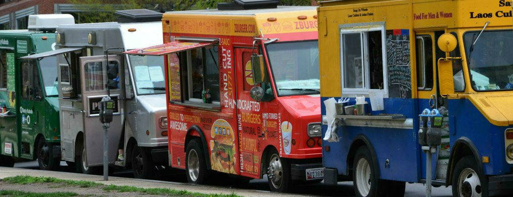 Row of Colorful Food Trucks Parked on City Street