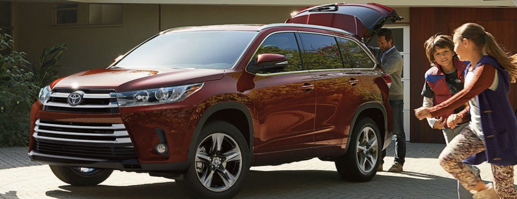 REd 2017 Toyota Highlander with Power Liftgate open in Driveway with kids playing