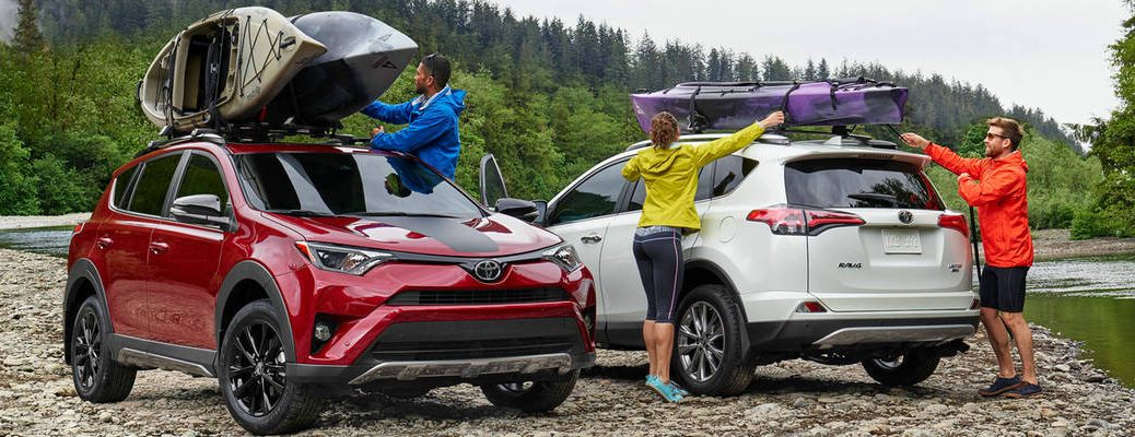 Red 2018 Toyota RAV4 Adventure with Kayaks and White 2018 Toyota RAV4 Limited with Kayak Next to River with People Unloading