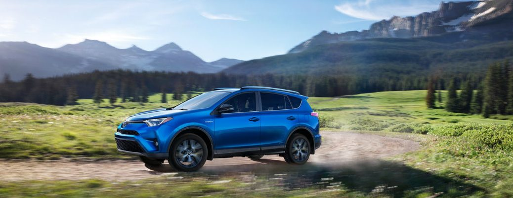 Electric Storm Blue 2018 Toyota RAV4 on Dirt Trail with Mountains and Pine Trees in Background