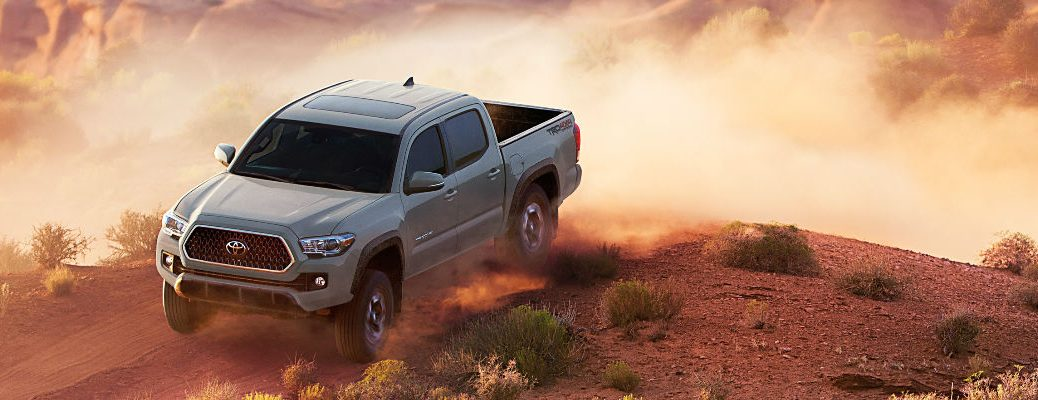 Gray 2018 Toyota Tacoma Kicking Up Dust in Red Sand Desert
