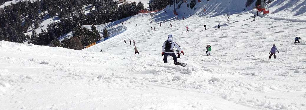 People Snowboarding Down a Ski Hill in Winter