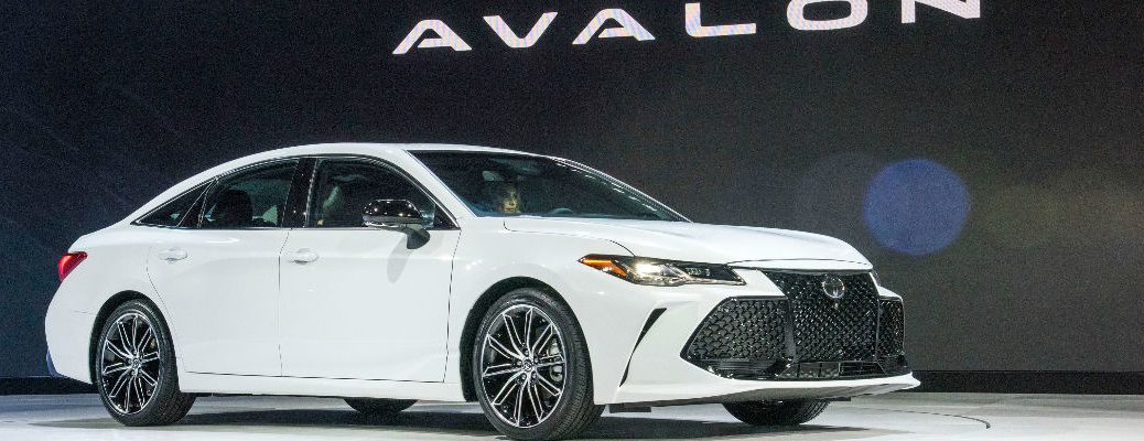 White 2019 Toyota Avalon Touring on Stage at 2018 Detroit Auto Show with Avalon Graphic in Background
