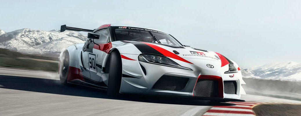 Red, White and Black Toyota GR Supra Concept on the Track with Mountains in the Background