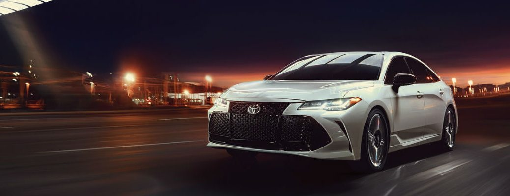 Wind Chill Pearl 2019 Toyota Avalon Driving on City Street at Night