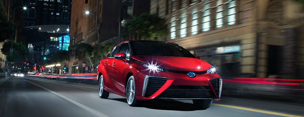 Red 2018 Toyota Mirai Driving on a City Street at Night