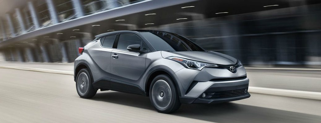 Silver Knockout Metallic R-Code with Black 2019 Toyota C-HR Driving on a City Street
