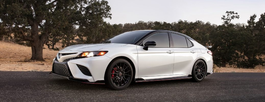 White and Black 2020 Toyota Camry TRD Side Exterior on a Country Road