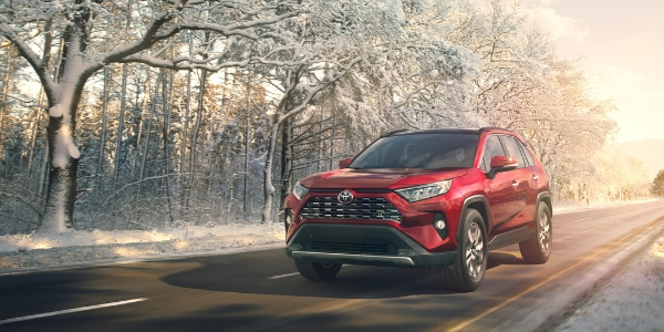 Red 2019 Toyota RAV4 Driving on a Snowy Road