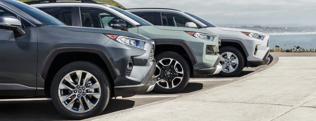 Gray, Green and White 2019 Toyota RAV4 Models Parked by Water with Close Up of Wheels and Tires