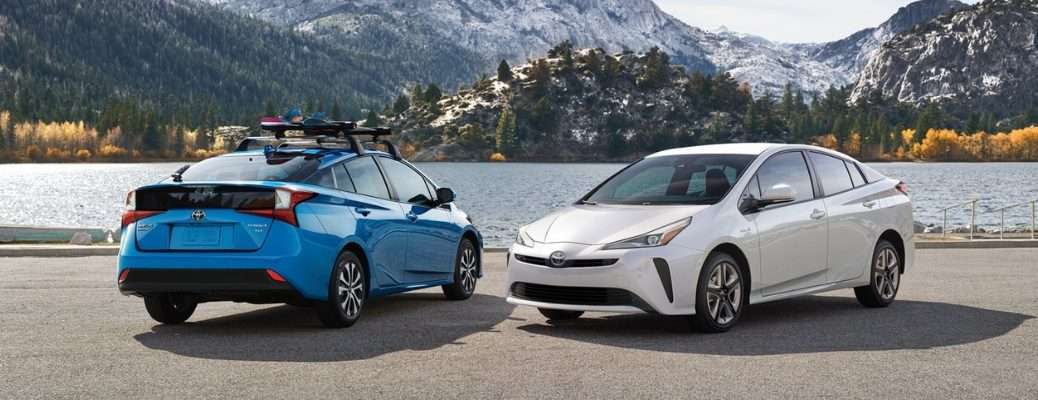 Blue and White 2019 Toyota Prius Models Next to Water with Mountains in Background