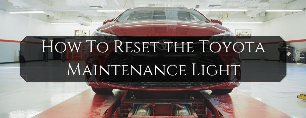 Red Toyota Camry in a Service Department on a Lift with Black Text Box and White How To Reset the Toyota Maintenance Light Text