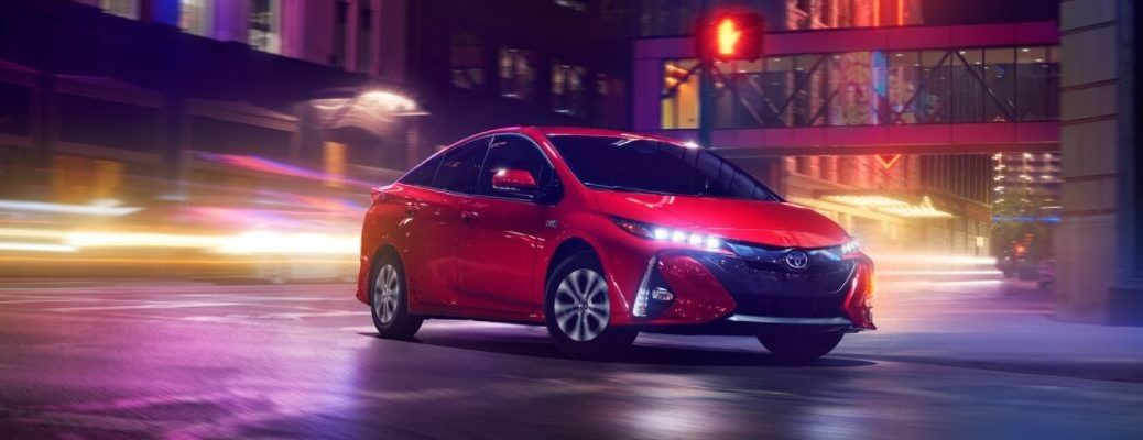 Red 2020 Toyota Prius Prime Driving on a City Street at Night