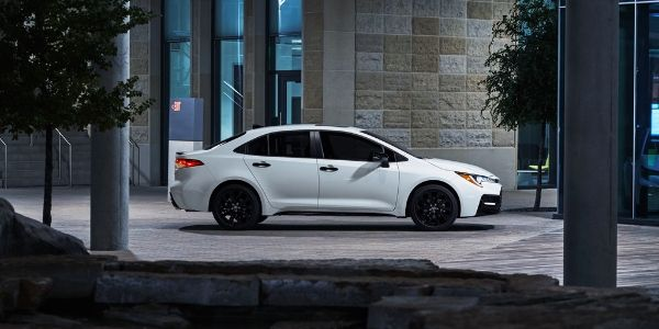 White 2020 Toyota Corolla Sedan Nightshade Edition Side Exterior in Front of Office Building