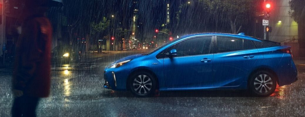 Blue 2020 Toyota Prius Driving on a City Street in the Rain