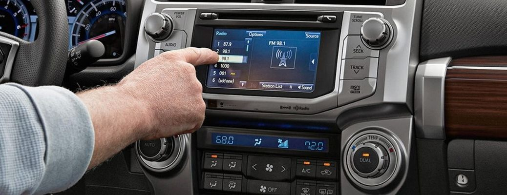 Man Using the Toyota Entune Touchscreen Audio System with CD Player in a 2019 Toyota 4Runner