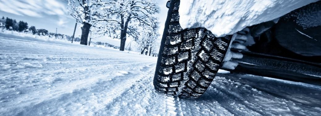 Close Up of Winter Tire Driving on Snow