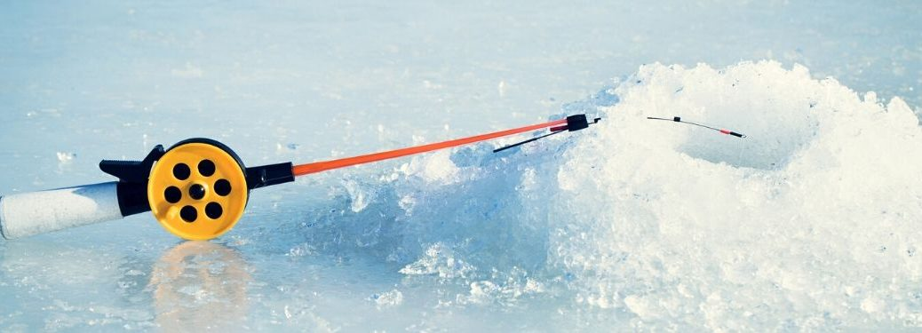 Close Up of Ice Fishing Pole Next to a Hole in the Ice