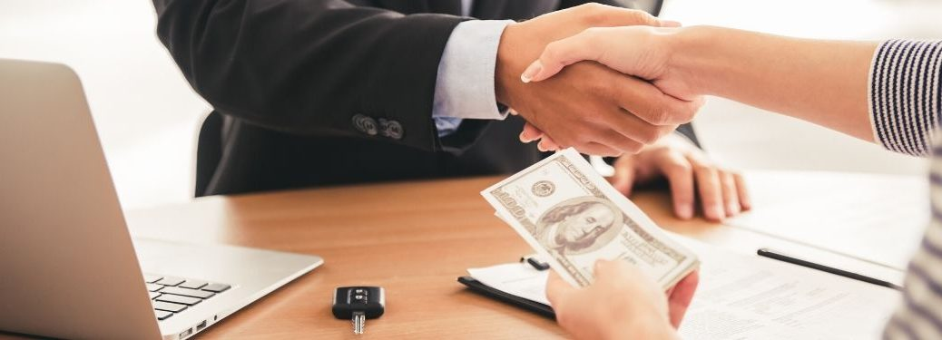 Dealer and Car Buyer Shaking Hands and Exchanging Cash