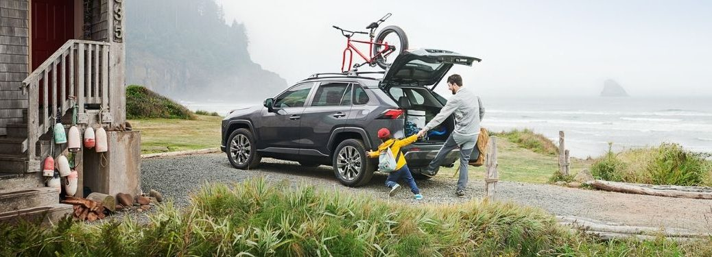 Man and Son Loading Cargo in the Back of 2020 Toyota RAV4