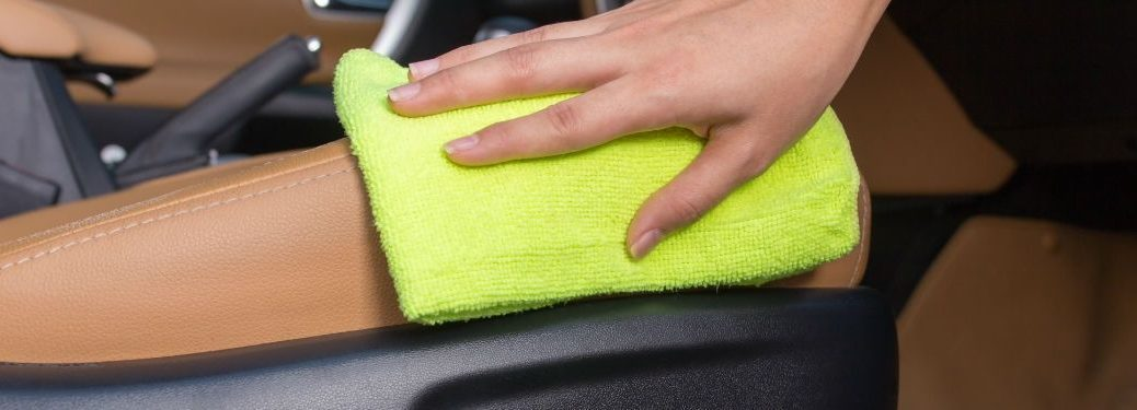 Close Up of a Woman's Hand Using a Cloth to Clean the Interior of a Car