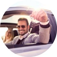 Man Holding a Key in a Driver's Seat of a New Car