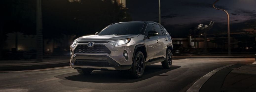 Silver 2020 Toyota RAV4 on a City Street at Night with Headlights On
