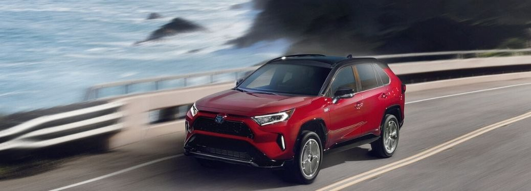 Red 2021 Toyota RAV4 Prime Driving on a Coast Road