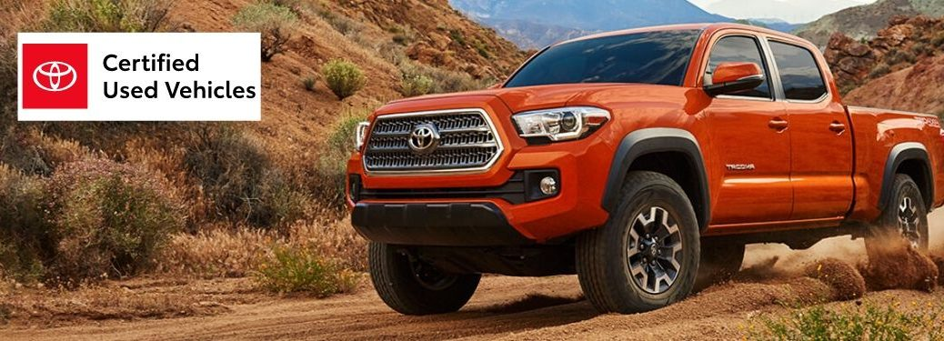 Orange Toyota Tacoma in a Desert with Red, White and Black Toyota Certified Used Vehicles Logo in Upper Left