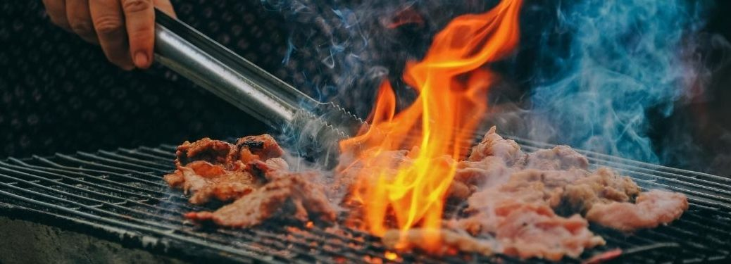 Man Using Tongs to Move Meat on a Flaming Grill