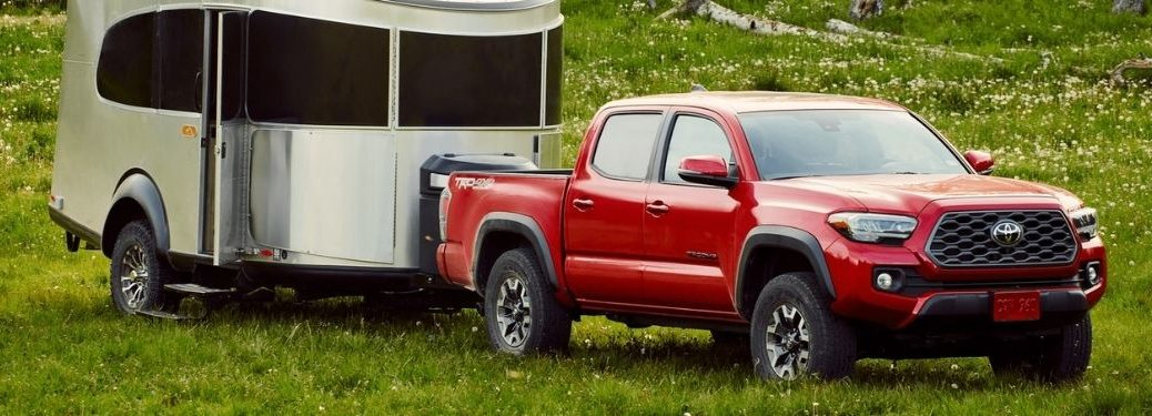 Red 2021 Toyota Tacoma Towing a Trailer in a Forest